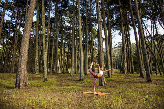 Hispanic woman practicing yoga in forest