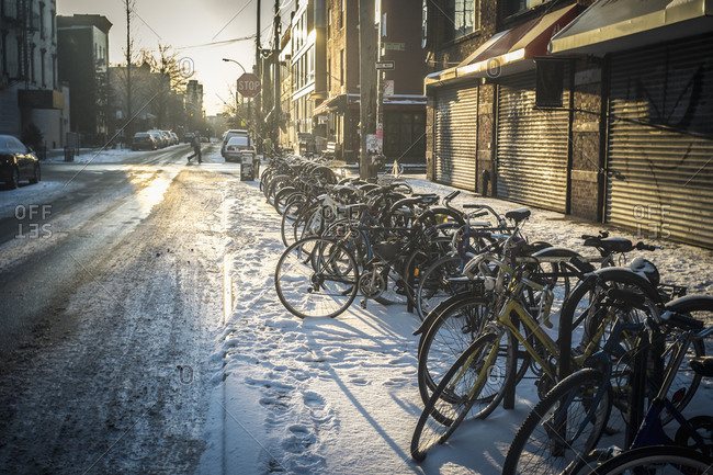 Bicycles parked in snow on city sidewalk, New York, New York, United States