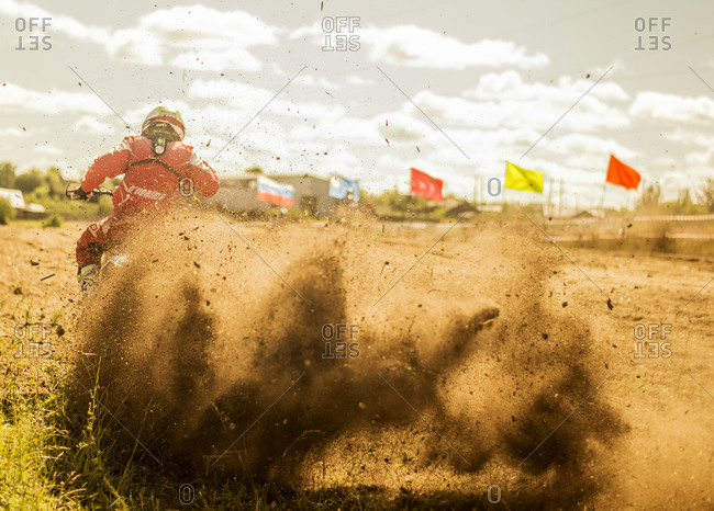 Caucasian motocross biker spraying dirt on race course