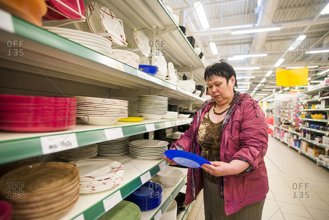 Caucasian woman shopping for dishes in store