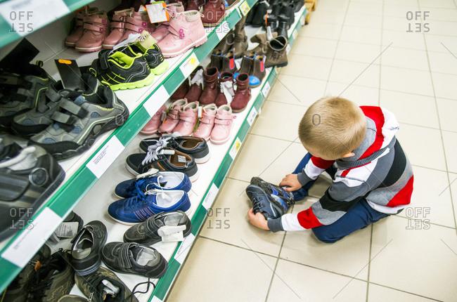Caucasian boy shopping in shoe store