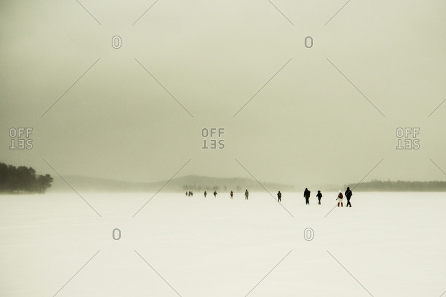 Caucasian hikers walking in snowy remote field