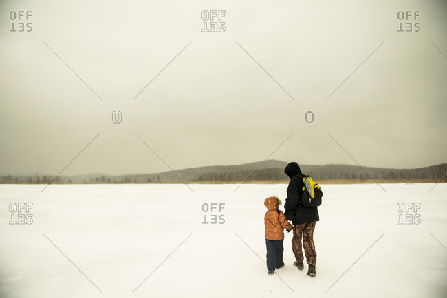 Caucasian father and son walking in snowy remote field