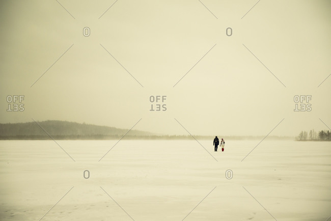Caucasian hikers walking in snowy remote field