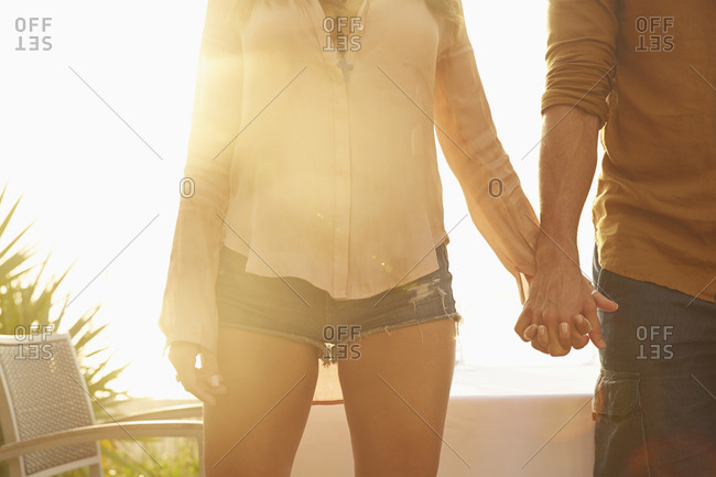 Hispanic couple holding hands outdoors