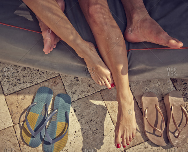 Close up of feet of Hispanic couple laying in cabana