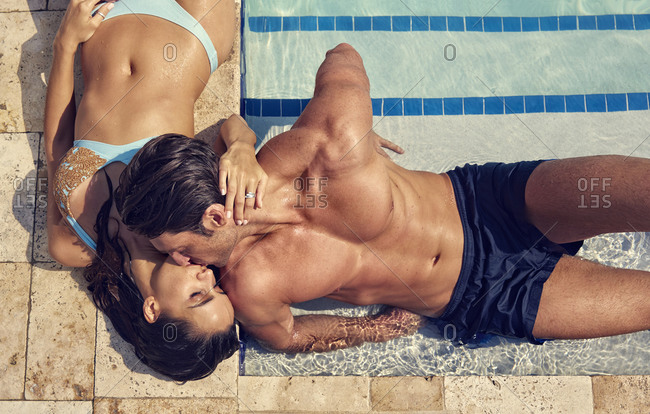 Hispanic couple kissing at swimming pool