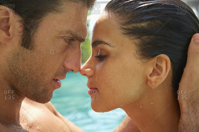 Close up of Hispanic couple touching noses in swimming pool