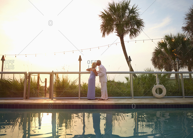 Older Caucasian couple kissing at swimming pool