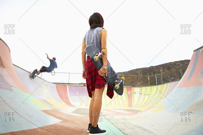Woman holding skateboard at skate park