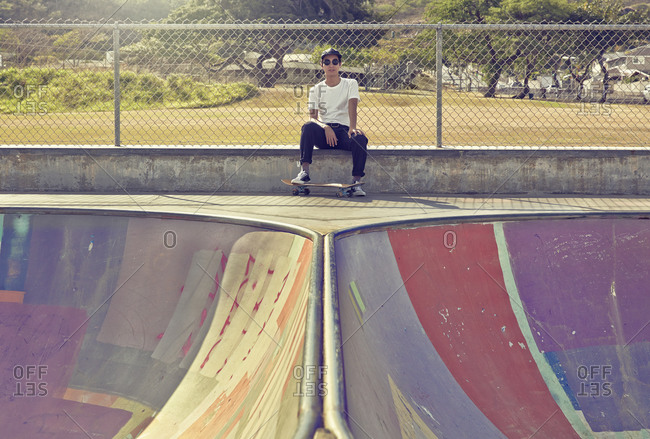 Mixed race man sitting on ramp in skate park
