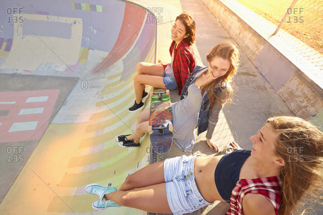 Friends sitting on ramp in skate park