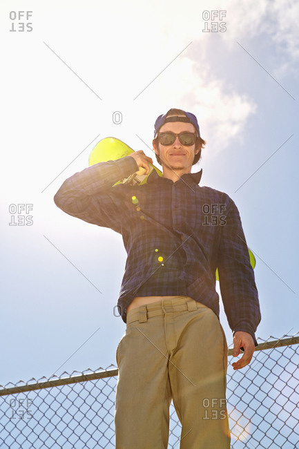 Low angle view of Caucasian man holding skateboard