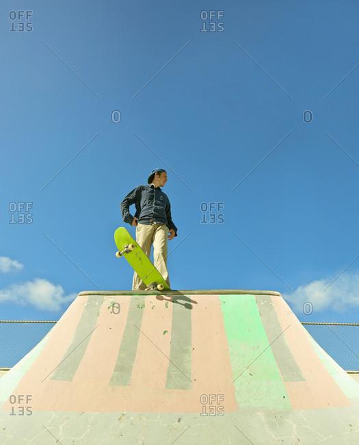 Caucasian man standing on skateboard at skate park