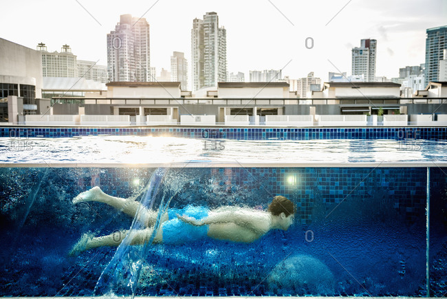 Caucasian man swimming in urban rooftop pool, Singapore