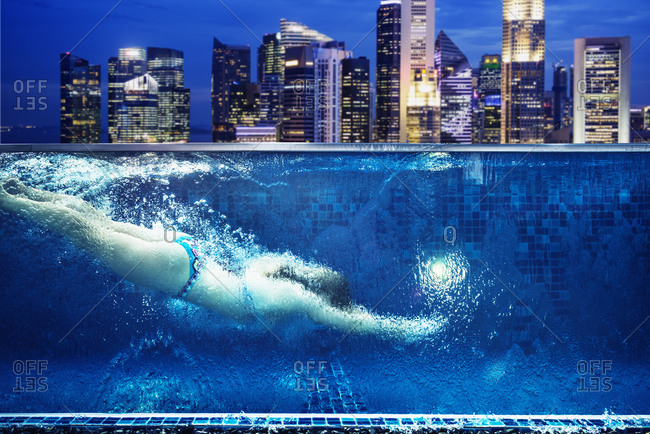 Caucasian woman swimming in urban rooftop pool in Singapore cityscape