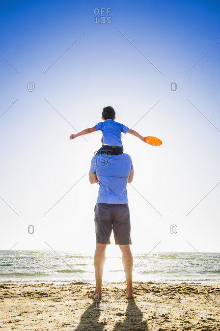 Caucasian father carrying son on shoulders on beach