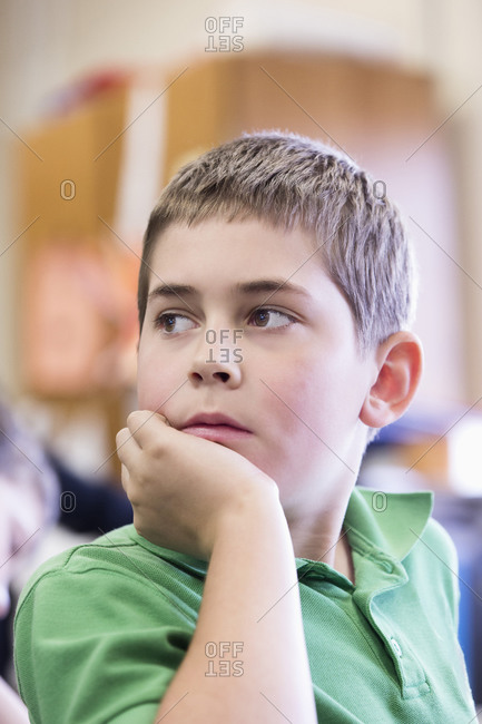 Close up of student looking over shoulder in classroom