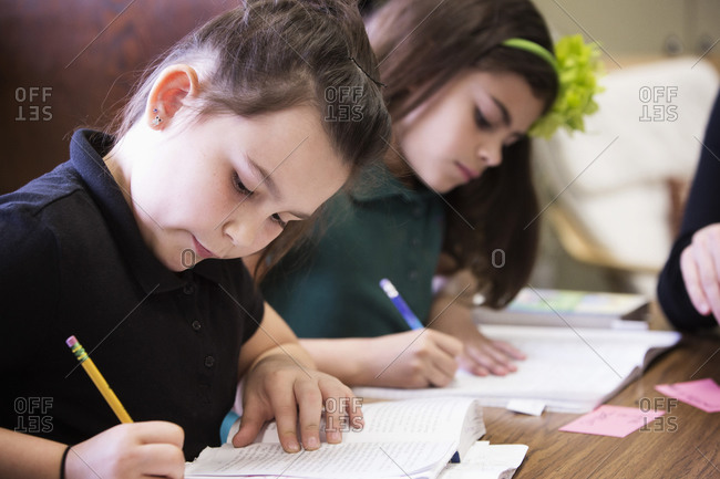 Students writing at desk in classroom