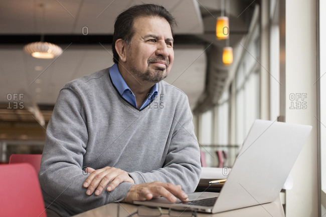 Hispanic man using laptop near window