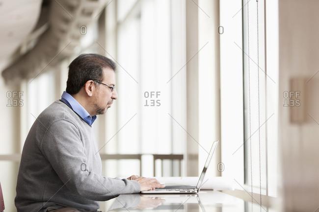 Hispanic businessman using laptop near window