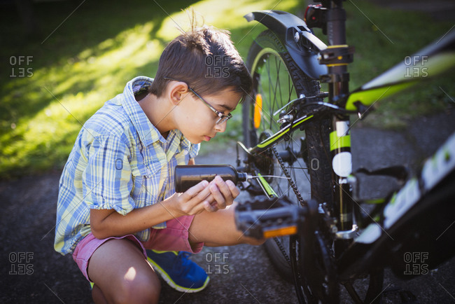 Mixed race boy oiling bicycle chain in backyard