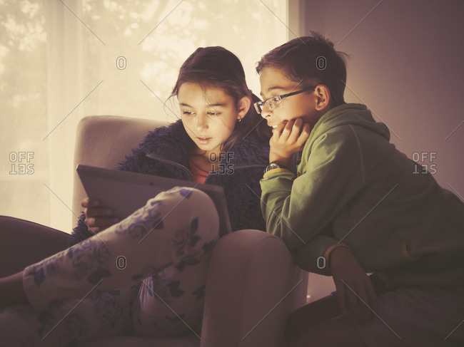 Mixed race children using digital tablet in living room