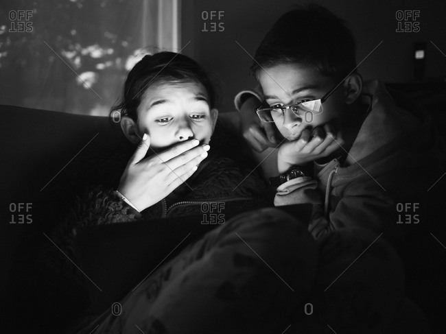 Mixed race children using digital tablet at night