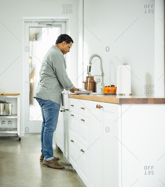 Mixed race man washing dishes in kitchen