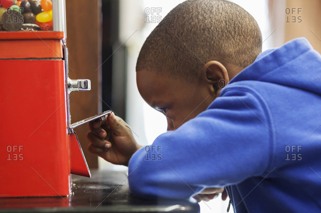 Black boy buying candy from coin-operated machine