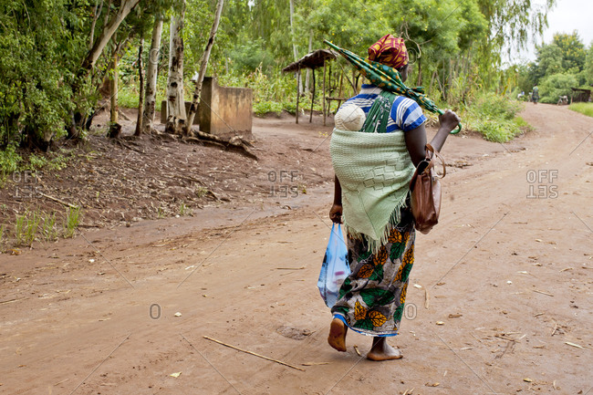 Mother carrying baby with traditional wrap on dirt road