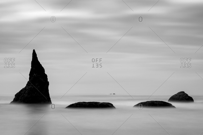 Fog over rock formations in ocean under cloudy sky