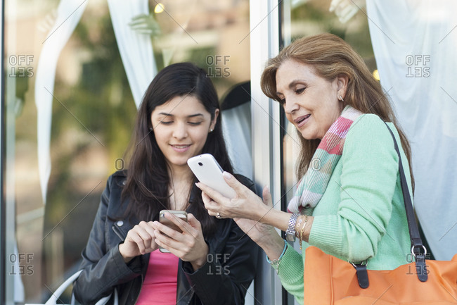 Mother and daughter using cell phones outdoors
