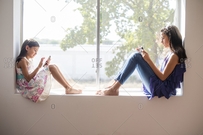 Sisters using technology in window