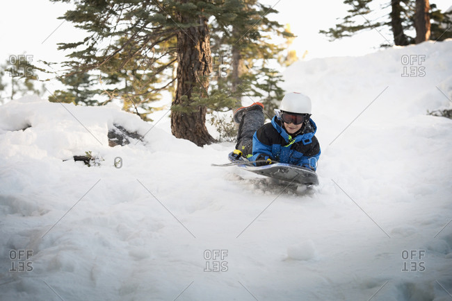 Mixed race boy sledding on snowy hillside