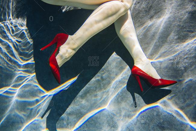 Legs of woman wearing high heels in swimming pool