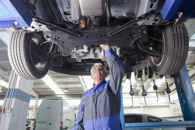 Older Hispanic mechanic repairing car in garage