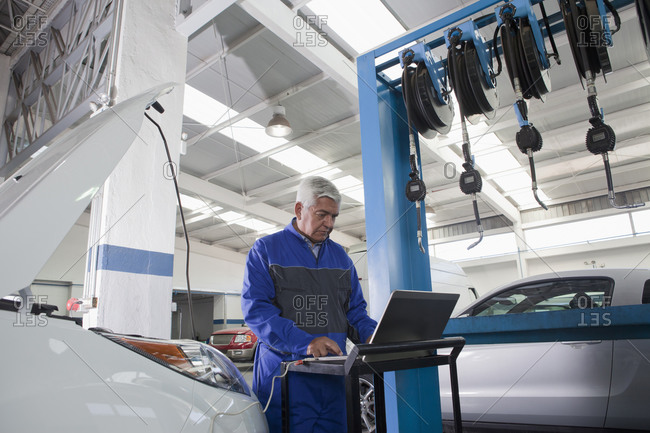 Older Hispanic mechanic using laptop in garage