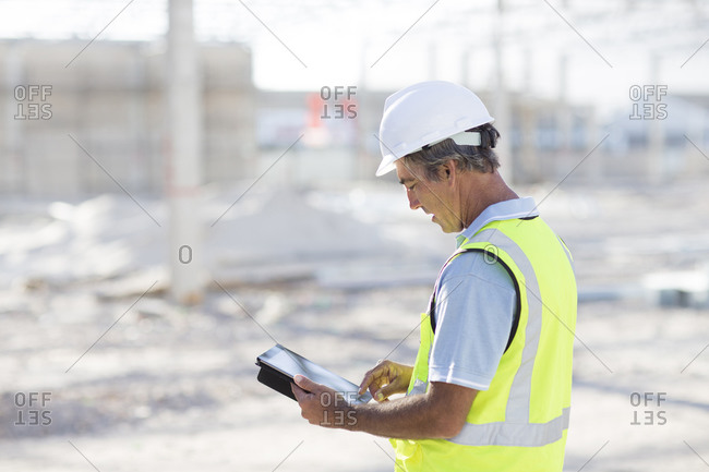 Caucasian architect using digital tablet at construction site