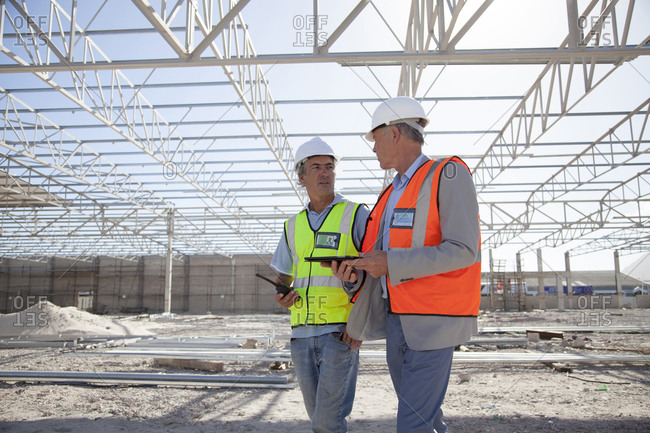 Caucasian architects talking at construction site