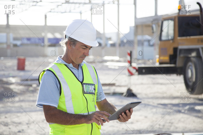 Caucasian construction worker using digital tablet at construction site