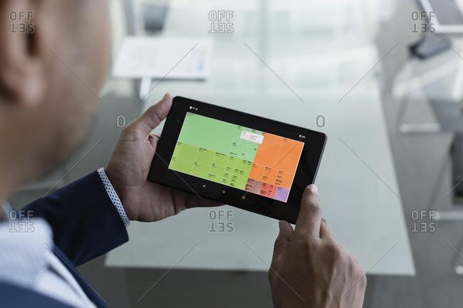 Hispanic businessman viewing graph on digital tablet