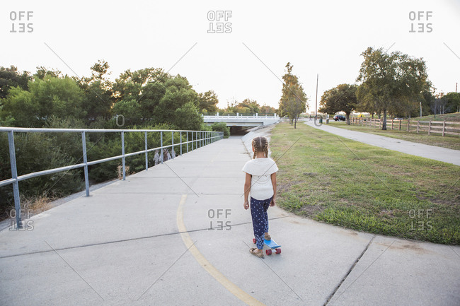 Mixed race girl riding skateboard in park