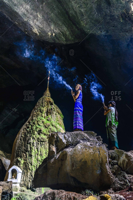 Asian women burning incense on rock formation in cave temple