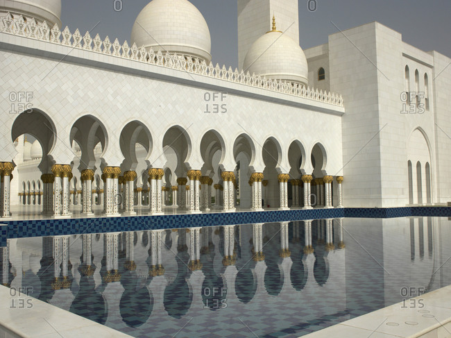 Ornate colonnade reflecting in still pool, Abu Dhabi, Abu Dhabi Emirate, United Arab Emirates