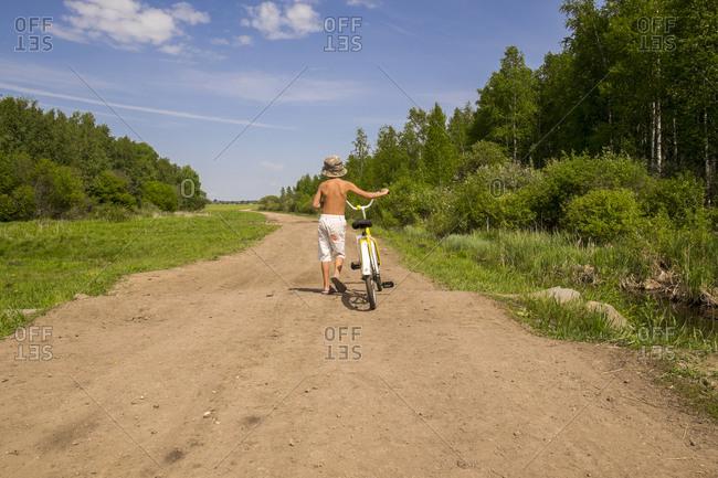 Mari boy walking bicycle on dirt path