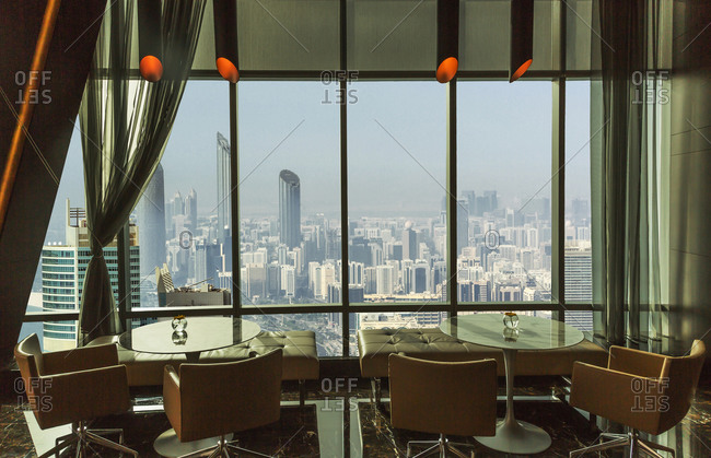 Restaurant tables overlooking Abu Dhabi cityscape, Abu Dhabi Emirate, United Arab Emirates