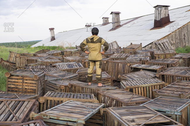 Mari man standing on wooden crates near roof