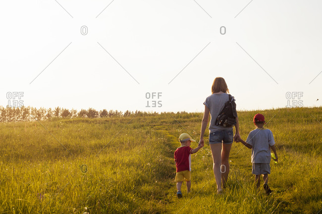 Mother and sons walking in rural field