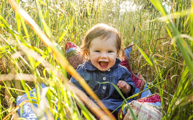 Caucasian baby girl sitting in tall grass